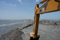 Photos tell different stories about sand berm effort to block oil spill